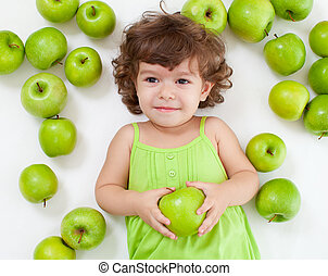 Adorable little girl lying with green apples