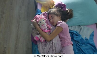 Adorable little girl night sleep in indoors the sofa bed and...