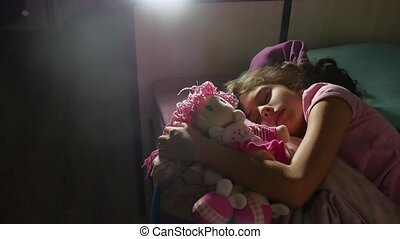 Adorable little girl night sleep in the sofa bed and hug her baby doll. girl brunette indoors teenager cute asleep on the bed
