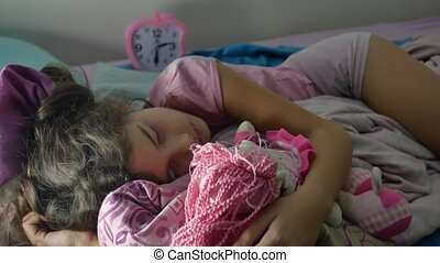 Adorable little girl night sleep in the sofa bed and hug...