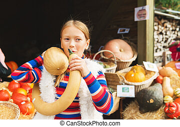 Adorable little girl of 8-9 year old choosing halloween pumpkin on farm market, having fun with unusual different kind of pumpkins