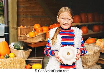 Adorable little girl of 8-9 year old choosing halloween pumpkin on farm market, holding white squash