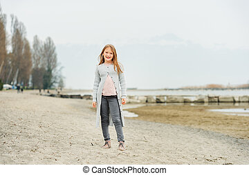 Adorable little girl of 8-9 years old playing by the lake,...