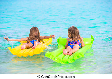 Adorable little girl on air inflatable mattress in the sea