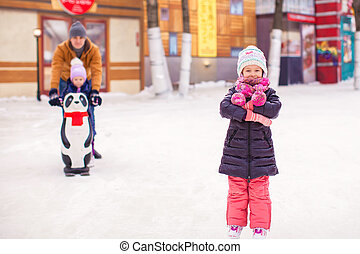 Adorable little girl on skating rink with father and cute sister in the background