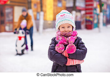 Adorable little girl on skating rink with father and sister in the background