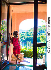 Adorable little girl on the balcony in exotic resort at summer vacatiom
