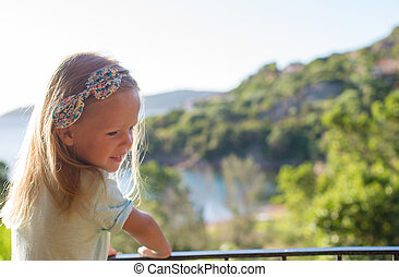 Adorable little girl on the balcony in exotic resort