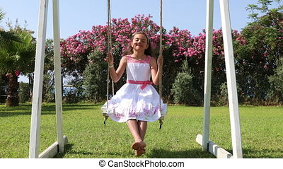 Adorable little girl on the swings - Adorable little girl in...