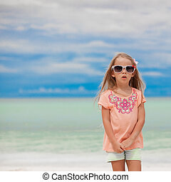Adorable little girl on tropical beach vacation