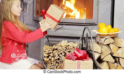 Adorable little girl opening christmas gifts near fireplace...