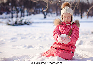 Adorable little girl outdoor in the park on cold winter day