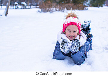 Adorable little girl outdoor in the park on winter day