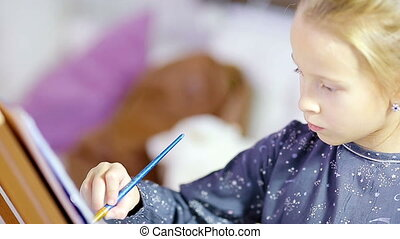 Adorable little girl painting a picture on easel indoor -...