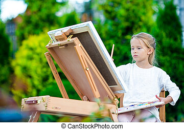 Adorable little girl painting a picture on easel outdoors