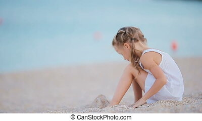 Adorable little girl playing at beach during european vacation