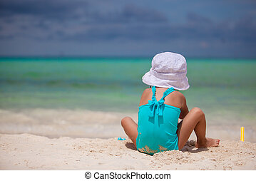 Adorable little girl playing at tropical beach during vacation