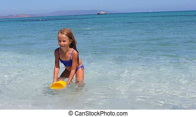 Adorable little girl playing at tropical beach
