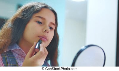 Adorable little girl playing make up. Happy kid painting her...