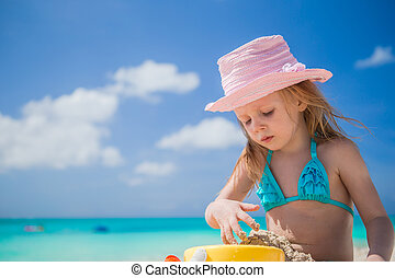 Adorable little girl playing on beach with white sand