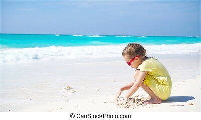 Adorable little girl playing on the beach with sand