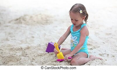 Adorable little girl playing on tropical beach