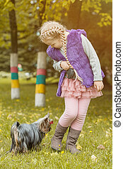 Adorable little girl playing with her puppy