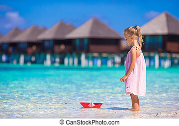 Adorable little girl playing with origami boat in turquoise sea