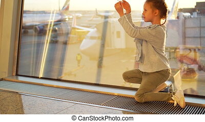 Adorable little girl playing with small model airplane in airport waiting for boarding. Concept of flying and airplane.