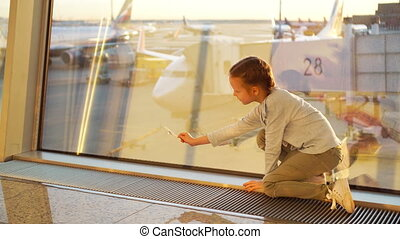 Adorable little girl playing with small model airplane in airport waiting for boarding