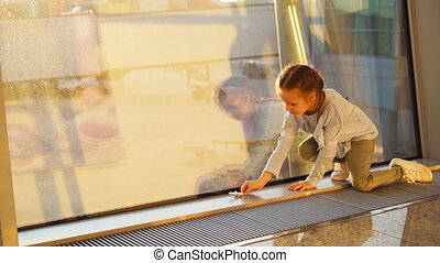 Adorable little girl playing with small model airplane toy in airport near big window. Concept of flying and airplane.