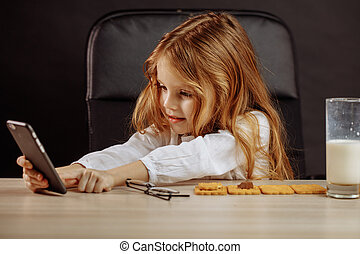 Adorable little girl playing with smartphone in Daddy s office