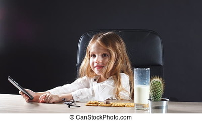 Adorable little girl playing with smartphone in Daddy s office.