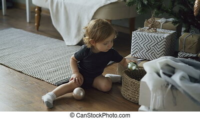 Adorable little girl playing with toy balls sitting near...
