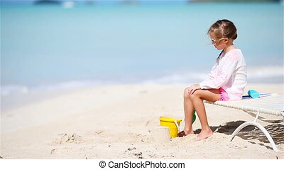 Adorable little girl playing with toys on beach vacation.