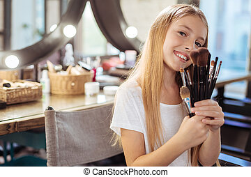 Adorable little girl posing with makeup brushes set