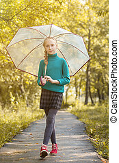 Adorable little girl posing with umbrella in park