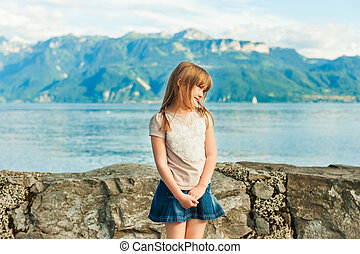 Adorable little girl resting by the lake on a nice warm summer day