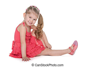 Adorable little girl sits on the floor