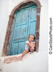 Adorable little girl sitting near blue door of old house in...