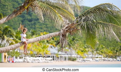 Adorable little girl sitting on palm tree during summer...