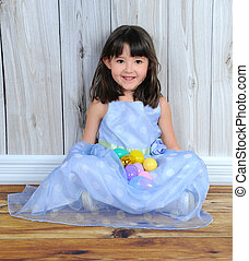 adorable little girl sitting with easter eggs in her lap