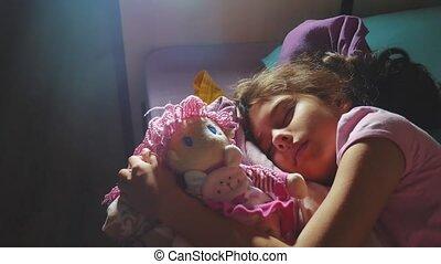 Adorable little girl sleep in the sofa bed and hug her baby...