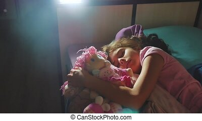 Adorable little girl sleep in the sofa bed and hug her baby...