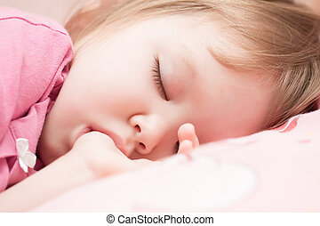 Adorable little girl sleeping in a bed