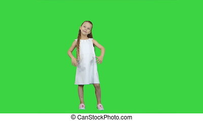 Adorable little girl smiling at camera and posing on a Green Screen, Chroma Key