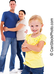 little girl standing in front of parents