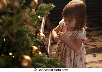 Adorable little girl standing near Christmas tree