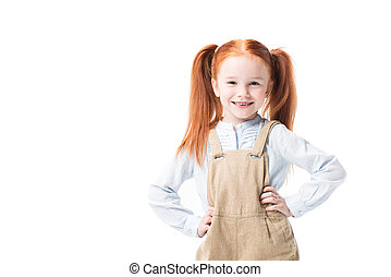 Adorable little girl standing with hands on waist and smiling at camera isolated on white