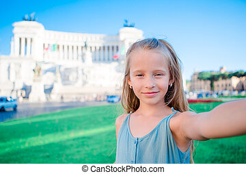 Adorable little girl taking selfie in front of Altare della ...